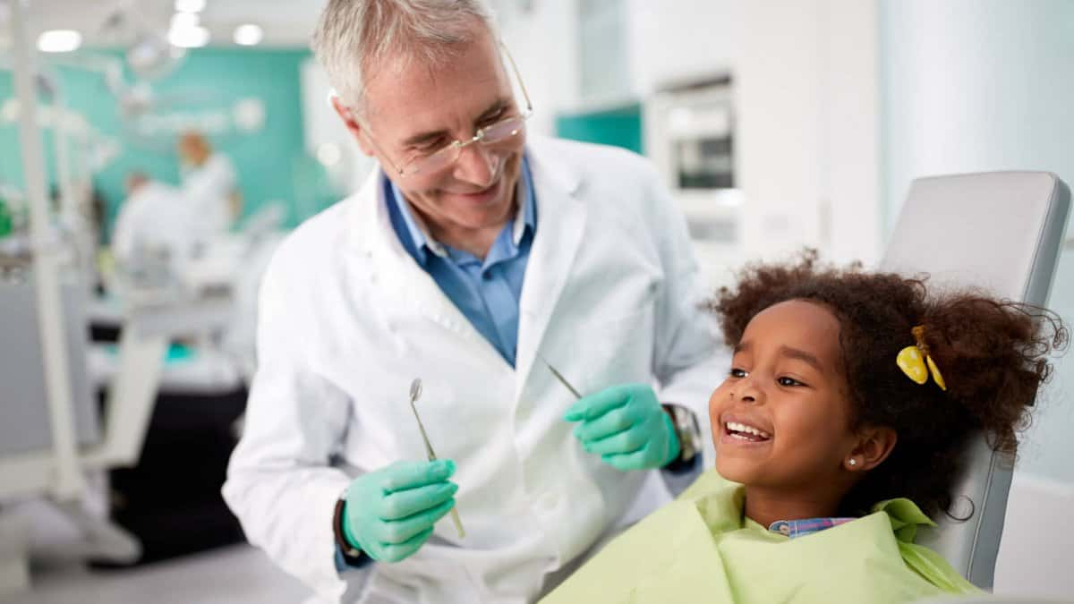 happy young girl in dental chair with dentist