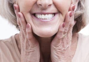 older woman smiling with dental crowns