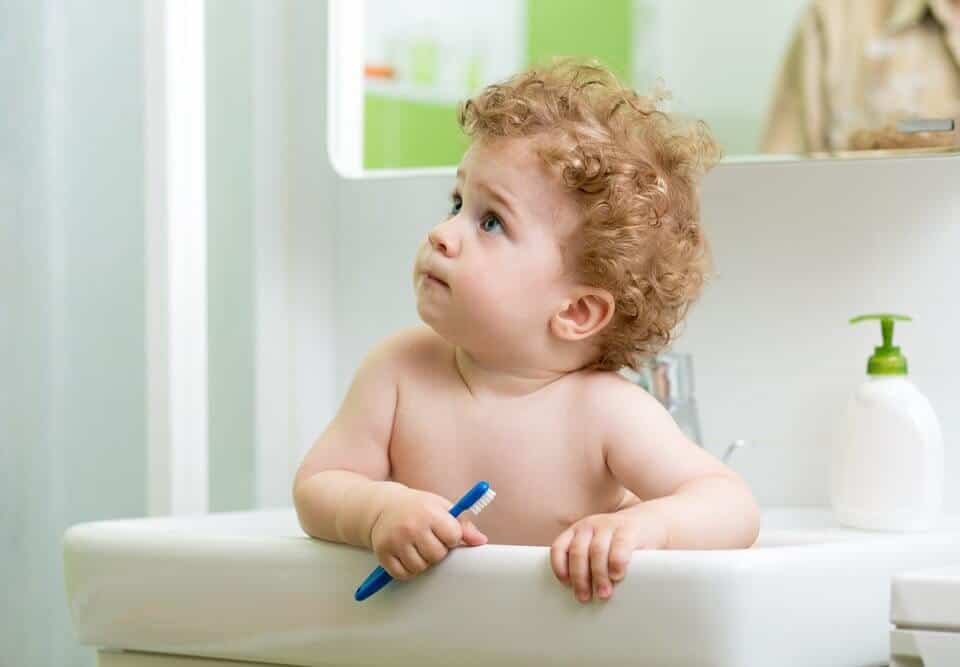 Baby in sink with toothbrush