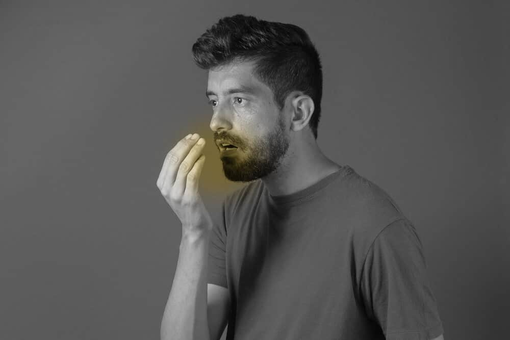 A man breathing into his hand and smelling his bad breath