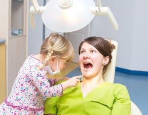 A child & Mom playing dentist so the child knows what to expect