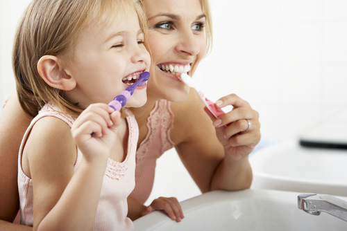 A child brushing their teeth with their parent