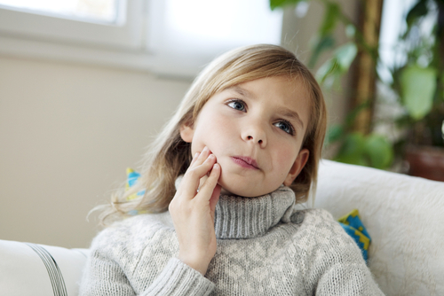 Child dealing with jaw pain from bruxism